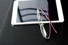vidrios y una sombra rosados en pantalla de la tableta blanca fotografía de archivo