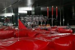Vidrios y velas en interior rojo con los espejos imagen de archivo