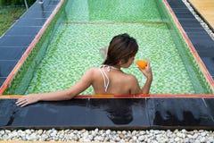 Vidro bebendo da menina asiática do suco de laranja na associação imagens de stock royalty free