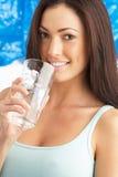 Vidro bebendo de mulher nova da água no estúdio Fotografia de Stock