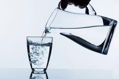 Vidro com água e o jarro Fotografia de Stock