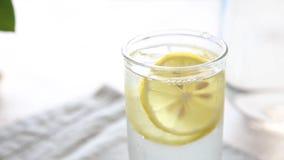 Vidro com água fria, com limão, gelo e hortelã video estoque
