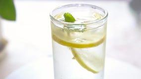 Vidro com água fria, com limão, gelo e hortelã vídeos de arquivo