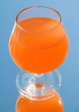 Vidro com água vermelha e reflexão em um espelho Fotografia de Stock Royalty Free