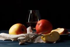 Vidro com aguardente de Calvados e as maçãs amarelas em uma tabela de madeira Foto de Stock