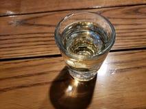 vidro com a bebida do tequila na tabela de madeira foto de stock