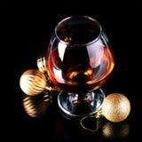 Vidro com bebida e bolas de um Natal Fotos de Stock Royalty Free