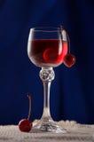 Vidro com cerejas e licor da cereja Imagem de Stock