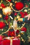 Vidro com champanhe em thepresent de Natal da árvore pela parte traseira sobre Fotografia de Stock Royalty Free