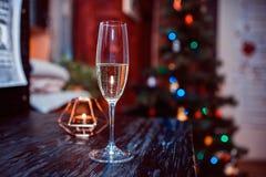 Vidro com champanhe na perspectiva de uma vela e de um abeto fotografia de stock royalty free