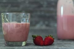 Vidro com milk shake, morangos e garrafa da morango no fundo foto de stock