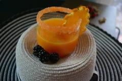 Vidro com suco de laranja, borda do açúcar da cenoura, uma fatia bonita de laranja e as amoras-pretas em um chapéu fêmea branco c Imagem de Stock