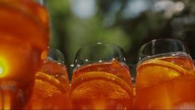 Vidro com uma bebida fria fora Os vidros com bebidas refletem as luzes do sol filme