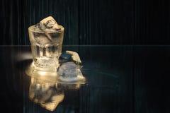 vidro cozinhado com vodca ou rum ou tequila frio e gelo com reflexão em uma tabela de vidro em um fundo de madeira preto foto de stock royalty free