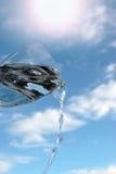 Vidro da água de encontro a um céu ensolarado Fotos de Stock