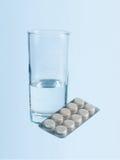 Vidro da água e dos comprimidos Fotos de Stock