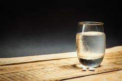 Vidro da água e dos comprimidos para uma manutenção Foto de Stock