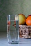 Vidro da água e dos frutos imagem de stock