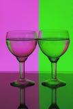 Vidro da água em um fundo cor-de-rosa e verde Fotografia de Stock Royalty Free