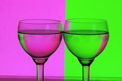Vidro da água em um fundo cor-de-rosa e verde Imagem de Stock