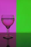 Vidro da água em um fundo cor-de-rosa e verde Imagem de Stock Royalty Free