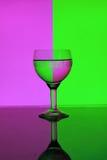 Vidro da água em um fundo cor-de-rosa e verde Imagens de Stock