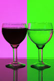 Vidro da água em um fundo cor-de-rosa e verde Imagens de Stock Royalty Free