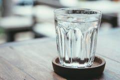 Vidro da água em uma tabela de madeira Fotografia de Stock Royalty Free