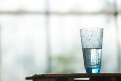 Vidro da água fria na tabela na frente do indicador fotos de stock
