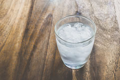 Vidro da água mineral fresca com os cubos de gelo na tabela de madeira com v Imagens de Stock Royalty Free