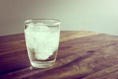 Vidro da água mineral fresca com os cubos de gelo na tabela de madeira com v Imagem de Stock Royalty Free