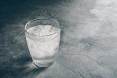 Vidro da água mineral fresca com os cubos de gelo na tabela do cimento com Foto de Stock
