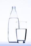 Vidro da água na frente da garrafa de água isolada no branco Fotos de Stock Royalty Free