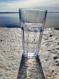 Vidro da água no beton com opinião do mar imagem de stock