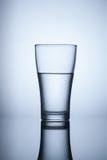 Vidro da água no fundo azul Fotografia de Stock