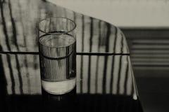 Vidro da água no piano fotos de stock royalty free