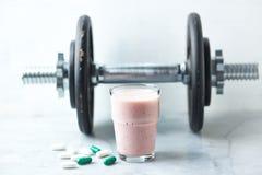 Vidro da agitação da proteína com leite e framboesas Ácidos aminados de BCAA, L - cápsulas da carnitina e um peso no fundo Porca  fotos de stock