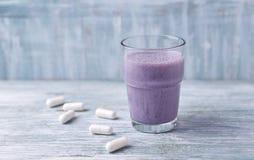 Vidro da agitação da proteína com leite e mirtilos e ácidos aminados de BCAA no fundo Nutrição do esporte imagem de stock