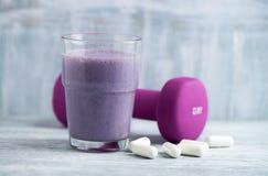 Vidro da agitação da proteína com leite e mirtilos Ácidos aminados de BCAA e um peso violeta no fundo Nutrição do esporte imagem de stock