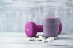 Vidro da agitação da proteína com leite e mirtilos Ácidos aminados de BCAA e um peso violeta no fundo Nutrição do esporte fotografia de stock