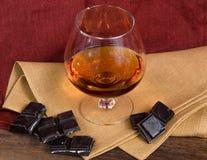 Vidro da aguardente e de um chocolate na tabela de madeira Foto de Stock