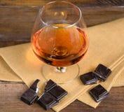 Vidro da aguardente e de um chocolate na tabela de madeira Imagens de Stock
