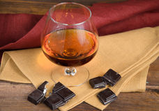 Vidro da aguardente e de um chocolate na tabela de madeira Fotos de Stock Royalty Free