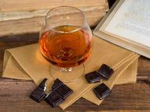 Vidro da aguardente e de um chocolate na tabela de madeira com livros Fotos de Stock Royalty Free