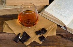 Vidro da aguardente e de um chocolate na tabela de madeira com livros Foto de Stock
