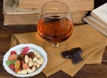 Vidro da aguardente e de um chocolate na tabela de madeira com livros Fotos de Stock