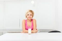 Vidro da bebida da mulher do leite em sua cozinha imagem de stock