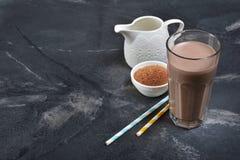 Vidro da bebida de leite de chocolate fria deliciosa com pó branco do jarro e de cacau fotos de stock