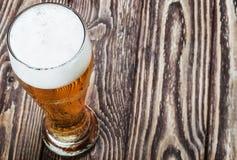 Vidro da cerveja clara fresca em uma tabela de madeira Foto de Stock Royalty Free