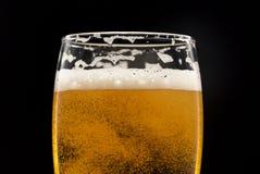 Vidro da cerveja com bolhas no close up preto Imagens de Stock Royalty Free